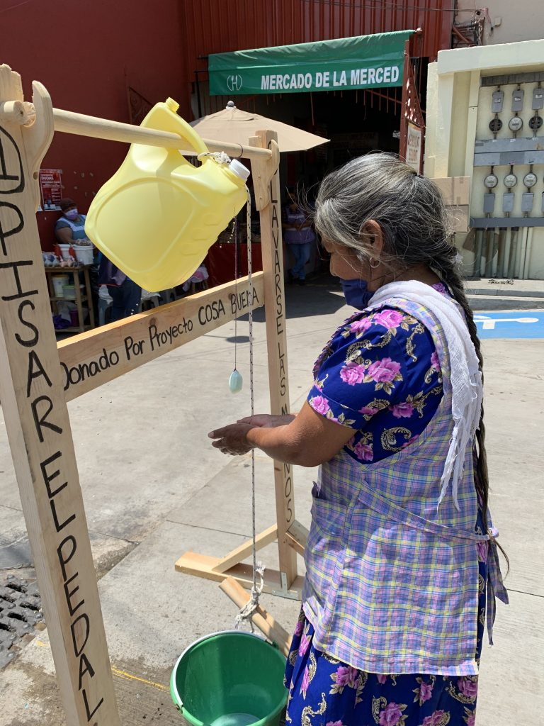 Woman washing her hands at handwashing station