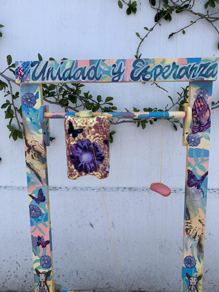 "Painted handwashing station with words ""Unidad y Esperanza"""